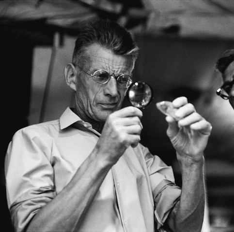 1964, New York, New York, USA --- Samuel Beckett on the set of his movie, , looking at a fish through a magnifying glass. --- Image by © Steve Schapiro/Corbis